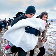 Refugees walk the unofficial refugee route from the Tabanovce, Macedonia train station, on their way to the next transportation center in Presevo, Serbia. Near Miratovac, Serbia, January 2016. According to UNHCR, the United Nations Refugee Agency, 67,415 refugees landed in Greece in January 2016, most of who traveled the route through Serbia on their way to Western Europe.
