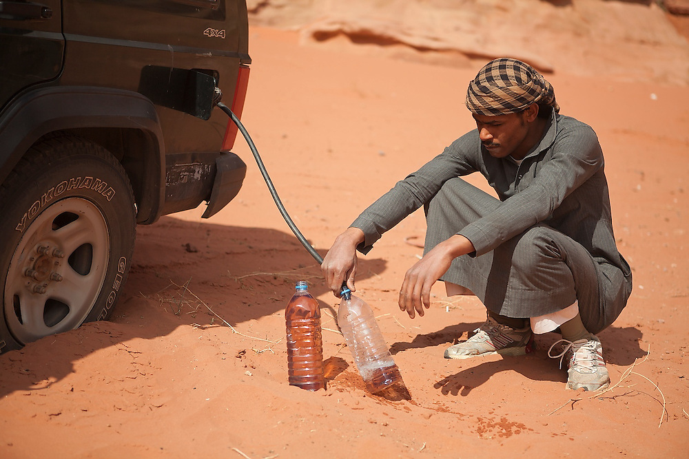 A Bedouin man siphons gasoline from a jeep in the desert in Wadi Rum, Jordan.