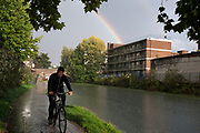 Cycling along the towpath of Regents Canal in East London, UK, during a heavy rain storm.