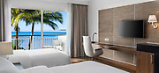 Photographie d'une chambre de l'hôtel Le Méridien Nouméa en Nouvelle Calédonie. la prise de vue présente 2 lits single avec une vue donnant sur le balcon et la mer.