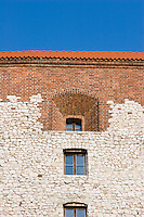 vertical shot showing wawel castle walls and window detail. the walls are part brick and part stone construction. bright sunshine and no clouds.