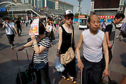 People at Beijing Railway Station. An elderly man in a vest top, a woman shielding here eyes from the sun and a young woman wearing a baseball cap.  Beijing Railway Station, China, is one of Beijing's main railway stations, opened in the 1950s, as can be seen from its architecture (which merges traditional architecture with 50s-design). It is located in the city's central location, just next to Jianguomen.