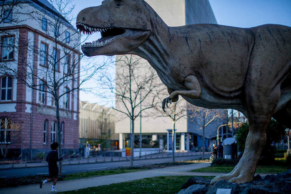 A park with a dinosaur sculpture in front of the Senckenberg  Museum in Frankfurt am Main on a normally very busy afternoon in emptiness because of the Corona virus.