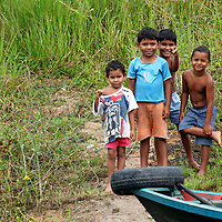 South America, Brazil, Amazon. Young boys playing on the riverbank pause to watch a boat pass on the Amazon.