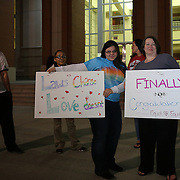 Supporters hold up signs as couples receive same sex marriage licenses at the Osceola County Courthouse in Kissimmee, Florida on  Tuesday, January 6, 2014.  (AP Photo/Alex Menendez)