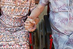 Two Elderly women holding hands,