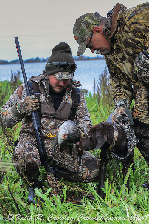 Young waterfowler with his six month old Chocolate lab puppy during the dog's first hunt.
