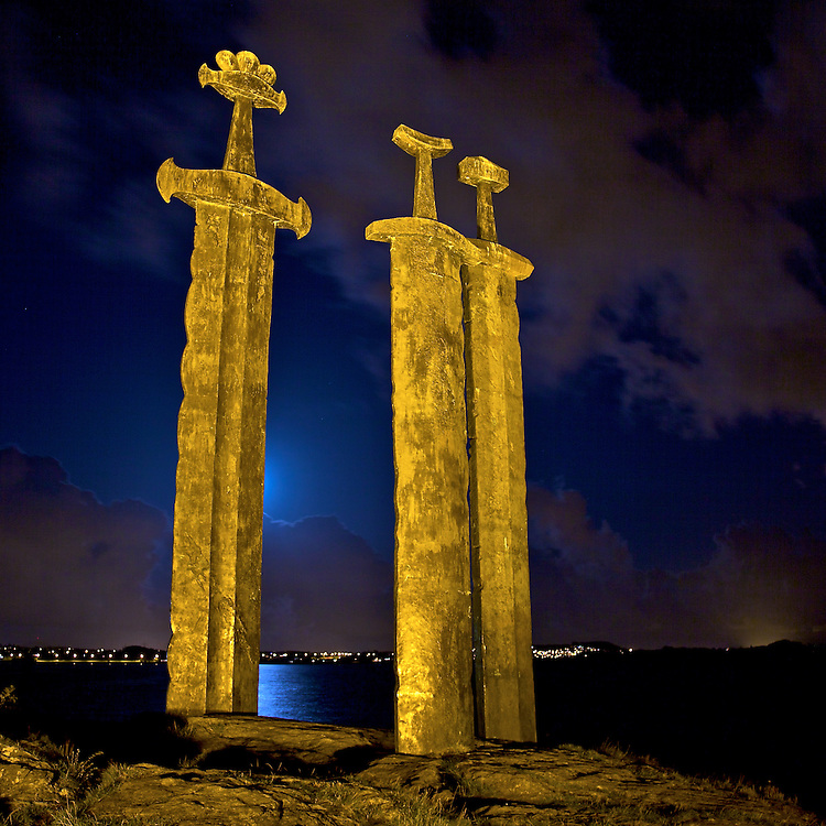 Three enormous bronze swords stand monument to the Battle of Hafrsfjord in the year 872, when Harald Hårfagre (Fairheaded Harald) united Norway into one kingdom. The monument was designed by local artist Fritz Røed and unveiled by Norway's King Olav in 1983.<br /> <br /> The swords, which are about 10 meters tall, stand for peace and unification. One sword is larger than the others. This was Fairheded Harald's sword. The crowns on the top of the swords represent the three districts that participated in the battle. The swords are planted in solid rock - representing peace. The monument is called Sverd i Fjell (Swords in Rock).