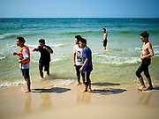 """13 FEBRUARY 2019 - SIHANOUKVILLE, CAMBODIA: Chinese tourists on Ocherteal Beach in Sihanoukville. There are about 80 Chinese casinos and resort hotels open in Sihanoukville and dozens more under construction. The casinos are changing the city, once a sleepy port on Southeast Asia's """"backpacker trail"""" into a booming city. The change is coming with a cost though. Many Cambodian residents of Sihanoukville  have lost their homes to make way for the casinos and the jobs are going to Chinese workers, brought in to build casinos and work in the casinos.      PHOTO BY JACK KURTZ"""