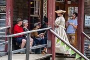 An actress in period costume conducts visitors on the Chinatown Tour in Barkerville Historic Town & Park, in British Columbia, Canada. Historically the main town of the Cariboo Gold Rush, Barkerville is now the largest living-history museum in Western North America. The town was named after Billy Barker from Cambridgeshire, England, who struck gold here in 1861, and his claim became the richest and the most famous. This National Historic Site nestles in the Cariboo Mountains at elevation 1200m (4000ft), at the end of BC Highway 26, 80 kilometres (50 mi) east of Quesnel. Gold here was first discovered at Hills Bar in 1858, followed by other strikes in 1859 and 1860. Wide publication of these discoveries in 1861 began the Cariboo Gold Rush, which reached full swing by 1865 following strikes along Williams Creek. To license this Copyright photo, please inquire at PhotoSeek.com. To license this Copyright photo, please inquire at PhotoSeek.com.