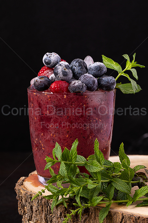 Berry smoothie decorated with frozen blueberries, raspberries and mint leaves.