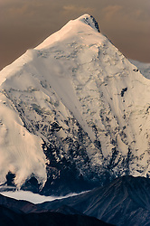 A smaller mountain (lower right) in the foothills of the Alaska Range is dwarfed by 11,940 foot Mt. Brooks at sunrise as seen from Wonder Lake in Denali National Park and Preserve in Alaska.