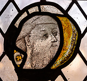 Stained glass window medieval fragment of face in close up, Christian Malford church, Wiltshire, England, UK