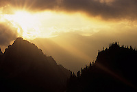 The sun sets behind the high peaks of the Tatoosh Mountains in Mount Rainier National Park, Washington.