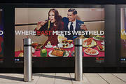 An aspirational poster landscape adorning a wall hoarding at Westfield City shopping centre in Stratford, home of the 2012 Olympics. A chic couple show us their success and affluence with a table full of food and drink. Situated on the fringe of the 2012 Olympic park, Westfield hosted its first day to thousands of shoppers eager to see Europe's largest urban shopping centre. The £1.45bn complex houses more than 300 shops, 70 restaurants, a 14-screen cinema, three hotels, a bowling alley and the UK's largest casino. It will provide the main access to the Olympic park for the 2012 Games and a central 'street' will give 75% of Olympic visitors access to the main stadium so retail space and so far 95% of the centre has been let. It is claimed that up to 8,500 permanent jobs will be created by the retail sector.