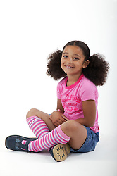 Young girl sitting cross legged on the floor,