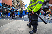 A Policeman holding to his baton as he observes an Extinction Rebellion climate protest near Covent Garden in central London on Monday, Aug 23, 2021. This is a two week planned of action against new fossil fuel investments. XR protestors are aiming to occupy parts of central London for two weeks from Monday, aiming to force the Government to halt all new investment in fossil fuels. (VX Photo/ Vudi Xhymshiti)