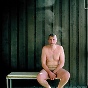 Portrait of a naked man sitting outside Vuorilammen sauna before ice swimming at the small lake of Vuorilampi, Jyvaskyla, Central Finland. Ice swimming takes place in a body of water with a frozen crust of ice, which requires a hole cutting in it.  In Finland, the ice swimming tradition has generally been connected with the sauna tradition and it is not seen as an ascetic or religious ritual, but as a way to cool off rapidly after staying in the sauna and as a stress relief.