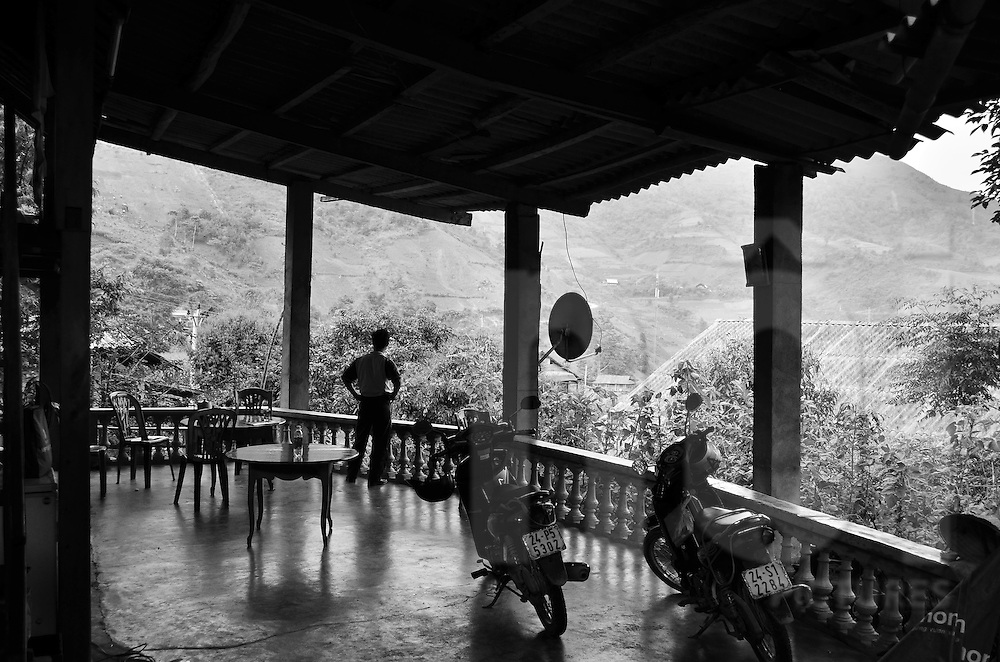 A man is standing with his hands on his hips, watching the view from the covered terrace of a house where two motorbikes are parked,  in Sapa surroundings, Lao Cai province, North Vietnam.