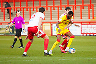Tom Pett of Stevenage FC tackles Walsall player for the ball during the EFL Sky Bet League 2 match between Stevenage and Walsall at the Lamex Stadium, Stevenage, England on 20 February 2021.