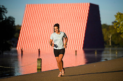 © Licensed to London News Pictures. 24/09/2018. London, UK. A woman jogs in front of The London Mastaba by Christo in the Serpentine Lake at sunrise on a cold Autumn morning in Hyde Park, central London. Photo credit: Ben Cawthra/LNP