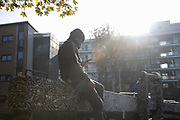 A man on his phone sits in the sun on the Regent Canal locks in Hackney during the second coronavirus national lockdownon on 7th of November 2020, East London, United Kingdom. The lockdown restrictions mean that people are only allowed to meet outside, in pairs and only if keeping social distance.