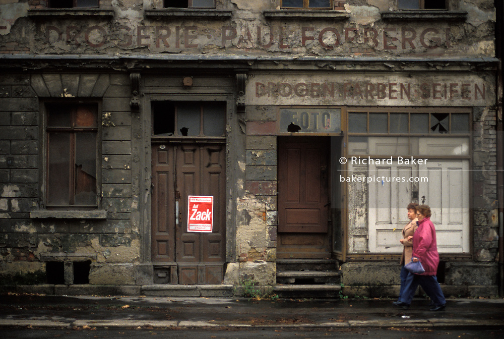 Six months after the fall of the Berlin Wall and the end of the Communist Eastern Bloc, two east German women walk past a closed and decaying Pharmacy and photography business where a poster advertising a New Germany weekly newspaper has been attached to a rotting door, on 15th June 1990, in Zwickau, eastern Germany (former DDR).