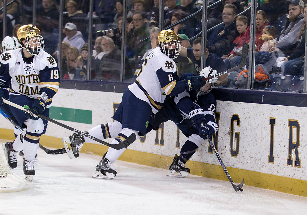 March 10, 2018:  Notre Dame defenseman Tory Dello (6) checks Penn State forward Evan Barratt (17) into the boards during NCAA Hockey game action between the Notre Dame Fighting Irish and the Penn State Nittany Lions at Compton Family Ice Arena in South Bend, Indiana.  Notre Dame defeated Penn State 3-2.  John Mersits/CSM