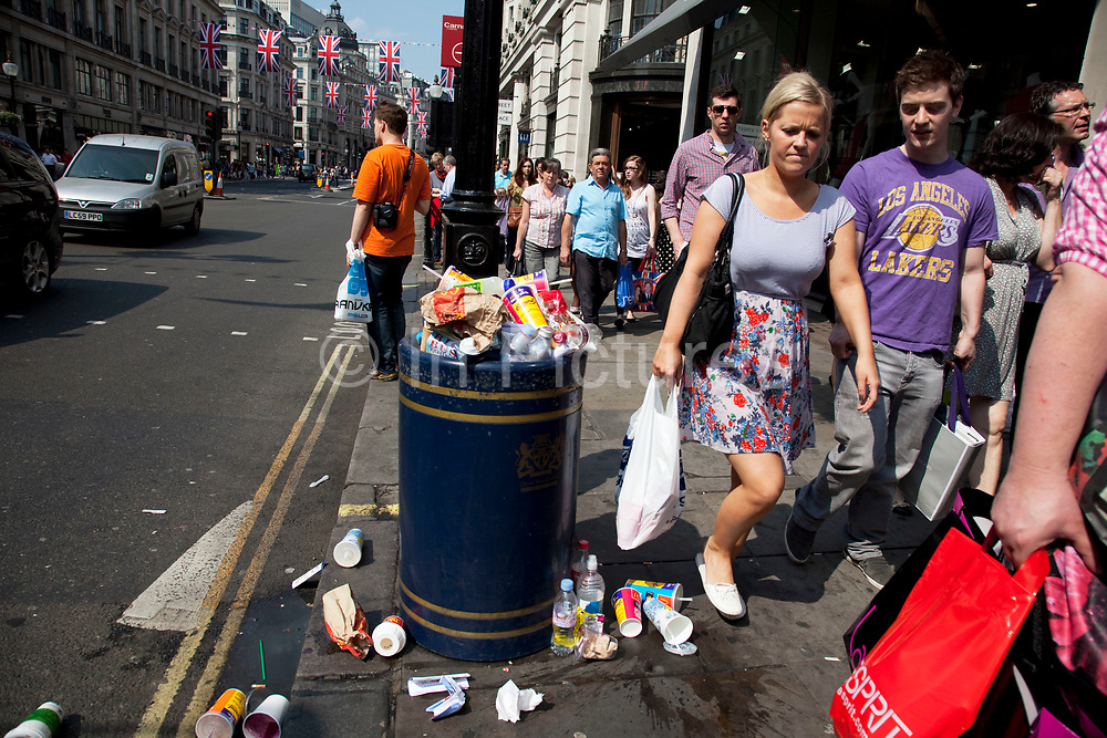 Overflowing bin and litter on Regent Street, central London. At certain times, especially weekends and public holidays, the volume of people in the area generates a big problem with trash. Rubbish piles high in certain places and proves unsightly for such an important area of London. People out shopping walk past and their reaction is plain to see.