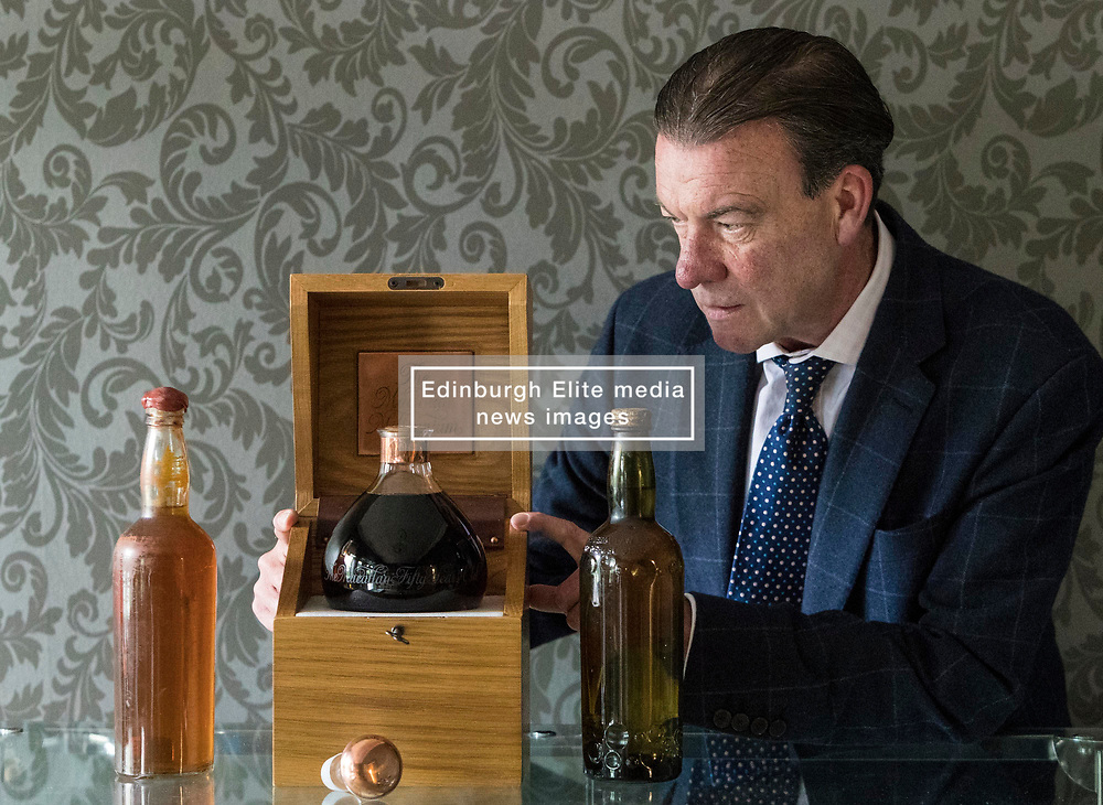 Bonhams whisky sale in Edinburgh on 7 June includes two salvaged bottles from the wreck of the SS Politician which were the inspiration for Compton MacKenzie's novel Whisky Galore. Also included in the sale is a 50 year-old Macallan Millennium Decanter distilled in January 1949.<br /> <br /> Pictured: Bonham's Whisky Consultant, Martin Green with Gilbey's - circa 1940 estimate £6,000 - £8,000, The Macallan Millennium Decanter - 50 year-old estimate £15,000 - £17,000 and Peter Dawson - circa 1940 estimate £4,000 - £6,000
