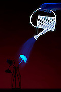 A flower in a vase comes to life as a glowing watering can sprinkles water on it.  Blacklight Photogrtaphy.