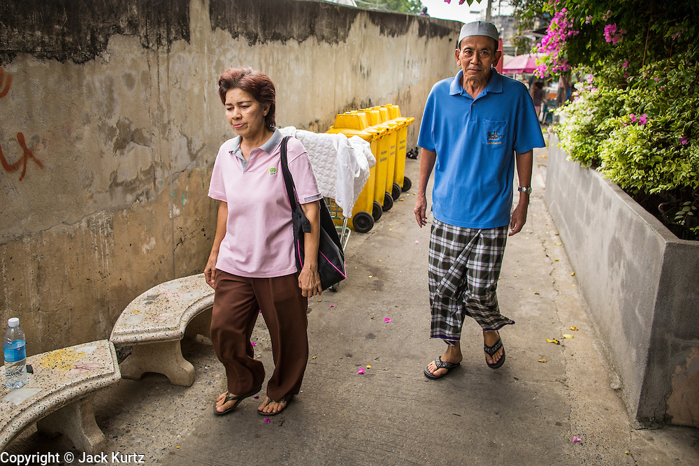"11 JANUARY 2013 - BANGKOK, THAILAND:     A Buddhist woman and Muslim man walk through the Ban Krua neighborhood in Bangkok. The Ban Krua neighborhood of Bangkok is the oldest Muslim community in Bangkok. Ban Krua was originally settled by Cham Muslims from Cambodia and Vietnam who fought on the side of the Thai King Rama I. They were given a royal grant of land east of what was then the Thai capitol at the end of the 18th century in return for their military service. The Cham Muslims were originally weavers and what is known as ""Thai Silk"" was developed by the people in Ban Krua. Several families in the neighborhood still weave in their homes.                 PHOTO BY JACK KURTZ"