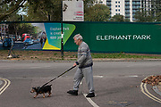 An elderly south Londoner walks his dog past a regeneration project hoarding at Elephant Park, Elephant & Castle, on 11th October 2016, in London, England. London borough of Southwark. Southwark Council's development partner, Lendlease is regenerating over 28 acres across three sites at the heart of Elephant & Castle, in what is the latest major regeneration opportunity in zone 1 London. The vision for the £1.5 billion regeneration is to build on the area's strengths and vibrant character in order to re-establish Elephant & Castle as one of London's most flourishing urban quarters. The Elephant & Castle regeneration is of a scale rarely seen in central London and includes almost 3,000 new homes, plus office, retail, community, leisure and restaurant space.