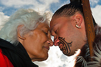 A Maori man with ta moko (facial tattoo) and an elderly Maori woman doing hongi (traditional Maori greeting) , Te Puia (New Zealand Maori Arts & Crafts Institute), Rotorua, New Zealand