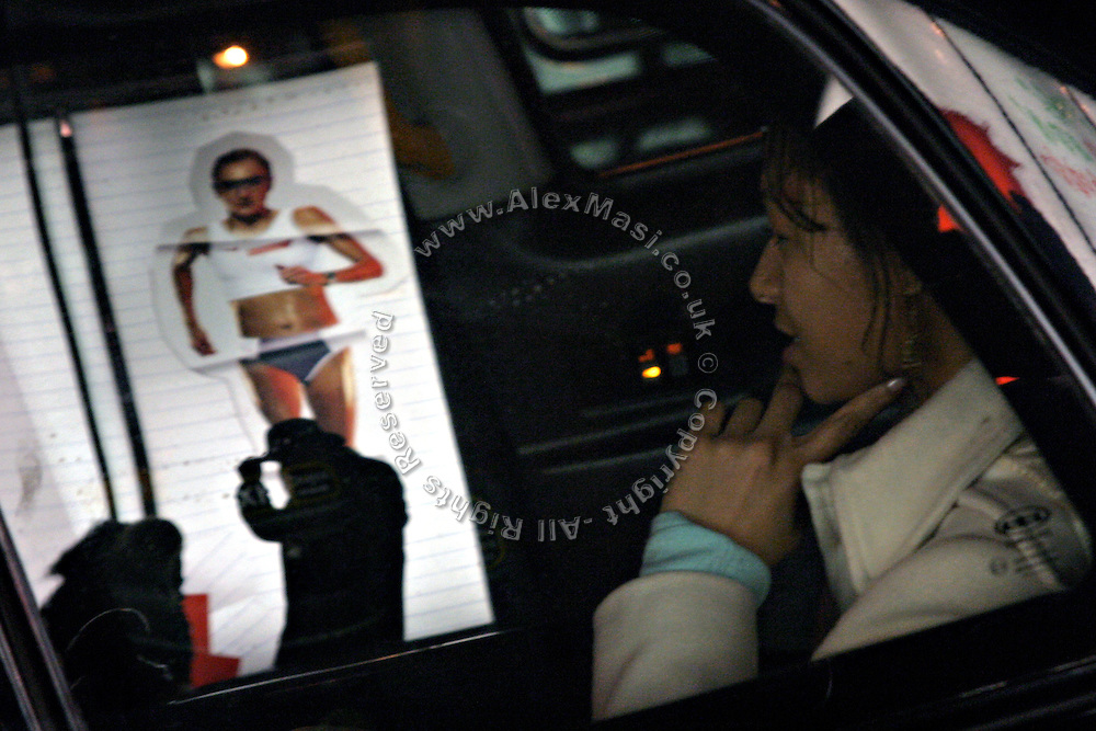 Woman in a taxi cab by the ëNike Towní shop, in London, on Thursday, Dec. 23, 2004.  On the shopís window is the picture of British athlete Paula Radcliffe, the marathon worldís record holder. She finished fourth at the last Olympic games held in Athens after a spectator grabbed her during the run. Getting home by taxi is a good alternative to the Christmas shopping stress. **ITALY OUT**