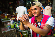 """26 SEPTEMBER 2012 - BANGKOK, THAILAND:  A porter waits for a customer in Khlong Toey Market in Bangkok. The streets and alleys in the market are too narrow for cars so many shoppers hire porters to help them carry their purchases out of the market. Khlong Toey (also called Khlong Toei) Market is one of the largest """"wet markets"""" in Thailand. The market is located in the midst of one of Bangkok's largest slum areas and close to the city's original deep water port. Thousands of people live in the neighboring slum area. Thousands more shop in the sprawling market for fresh fruits and vegetables as well meat, fish and poultry.    PHOTO BY JACK KURTZ"""