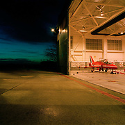 A red Hawk jet aircraft belonging to the elite 'Red Arrows', Britain's prestigious Royal Air Force aerobatic team, is parked in the hangar at RAF Scampton, Lincolnshire, the home base for the squadron. Night is falling with only blue daylight remaining in the western sky and the warm light from the hangar spills out of the giant open doors on to the concrete. The aircraft awaits attention from the engineer's night-shift who service and maintain all 11 of the famous red aerobatic jets before flying the next morning. The hangar, an original World War 2 shelter for the Lancaster bombers of 617 Dambusters squadron who attacked the damns of the German Ruhr valley on 16th May 1943 using the Bouncing Bomb. The Red Arrows use this and nearby offices administrative nerve-centre for the 90-plus displays they perform a year.