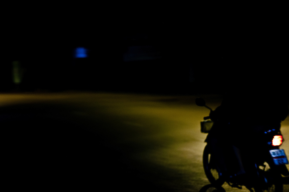 A motor scooter drives off into the night in Chiang Mai, Thailand.