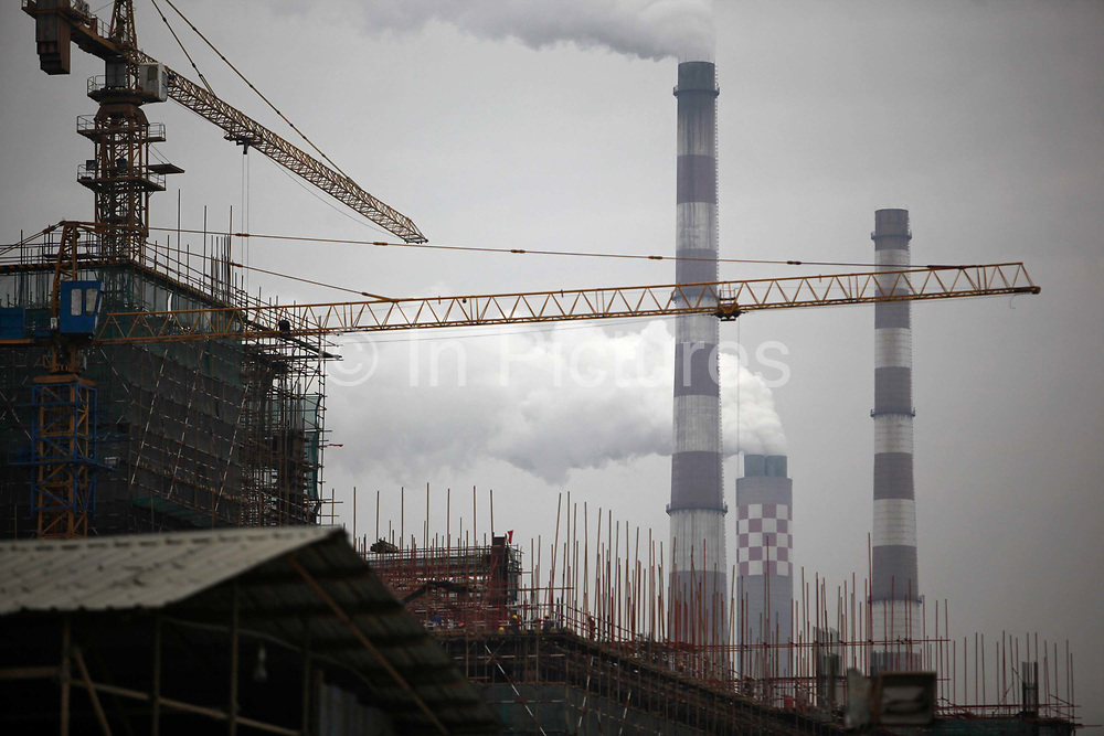 Smoke stacks from a power plant spew out exhaust as workers operate to construct a new power generating unit  in Changshu, Jiangsu Province, China on 18 March, 2011.  China is quickly pushing to expand its alternative energy options while currently a majority of its rapidly expanding appetite for electricity is satisfied by coal, which the country has an abundant supply of.