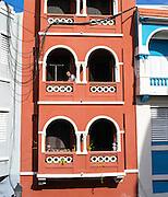 A man on his balcony on a Sunday morning; Colorful building facade, Old San Juan/Viejo San Juan.