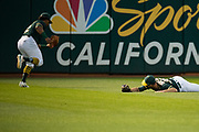 Oakland Athletics left fielder Khris Davis (2) scoops up a missed fly ball by Oakland Athletics center fielder Jaycob Brugman (38) against the San Francisco Giants at Oakland Coliseum in Oakland, California, on July 31, 2017. (Stan Olszewski/Special to S.F. Examiner)