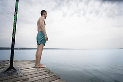 Mature man standing on pier and looking at view, Bavaria, Germany