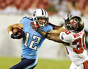 August 17, 2012, Tampa, Florida, USA;   D.J. Woods(12) of the Tennessee Titans gives a stiff arm to the face of Cornerback Marquese Wheaton(30) of the Tampa Bay Buccaneers after a catch during a preseason game.