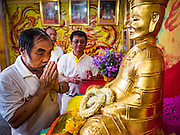 12 OCTOBER 2015 - BANGKOK, THAILAND:   A man makes merit by leaving flowers in a shrine in Chinatown on the first day of the Vegetarian Festival in Bangkok's Chinatown. The Vegetarian Festival is celebrated throughout Thailand. It is the Thai version of the The Nine Emperor Gods Festival, a nine-day Taoist celebration beginning on the eve of 9th lunar month of the Chinese calendar. During a period of nine days, those who are participating in the festival dress all in white and abstain from eating meat, poultry, seafood, and dairy products. Vendors and proprietors of restaurants indicate that vegetarian food is for sale by putting a yellow flag out with Thai characters for meatless written on it in red.     PHOTO BY JACK KURTZ