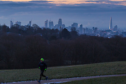 """A man runs through Hampstead Heath as distant clouds brood over the city's skyline. The threatened snow from """"The Beast From The East"""" weather system doesn't materialise overnight in London leaving a crisp, clear morning, seen from Hampstead Heath in North London. London, February 27 2018."""