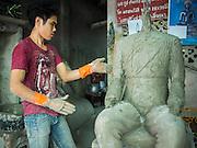 10 JANUARY 2014 - BANGKOK, THAILAND:  A man works on a statue of King Chulalongkorn, Rama V, in the Amulet market in Bangkok.    PHOTO BY JACK KURTZ