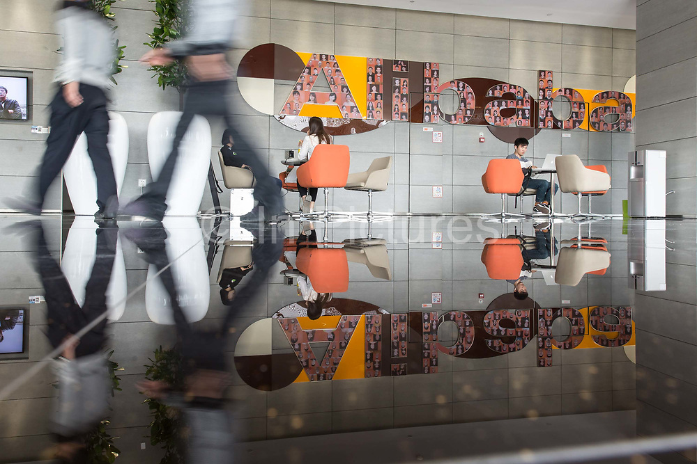 Employees walk through a building lobby at the Alibaba Group Holding Ltd. headquarters in Hangzhou, China, on Tuesday, Oct. 13, 2015.