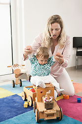 Baby mother playing toy engine train sitting