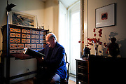 Antonio Tabucchi, italian professor and writer, sitting at his working desk in his home in Lisbon, holding the manuscript of his next book.