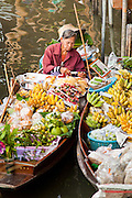 "10 JULY 2011 - DAMNOEN SADUAK, RATCHABURI, THAILAND: A vendor in the floating market in Damnoen Saduak, Thailand, sells fresh fruit from his boat. The Thai countryside south of Bangkok is crisscrossed with canals, some large enough to accommodate small commercial boats and small barges, some barely large enough for a small canoe. People who live near the canals use them for everything from domestic water to transportation and fishing. Some, like the canals in Amphawa and nearby Damnoensaduak (also spelled Damnoen Saduak) in Rajburi  province (also spelled Ratchaburi) are also relatively famous for their ""floating markets"" where vendors set up their canoes and boats as floating shops.     PHOTO BY JACK KURTZ"
